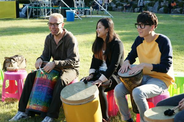 축제 참가자들이 세계 각국의 타악기를 두드리며, 홍캠프의 두그루 드럼서클을 즐기고 있다.